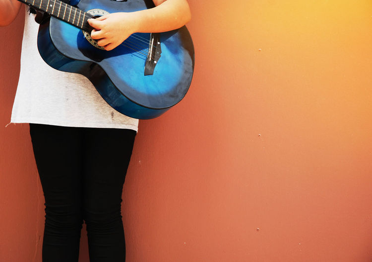 beautiful girl teen playing blue acoustic guitar Arts Culture And Entertainment Blue Casual Clothing Copy Space Day Hand Holding Human Body Part Human Hand Leisure Activity Lifestyles Midsection Music Musical Equipment Musical Instrument One Person Real People Standing Wall - Building Feature