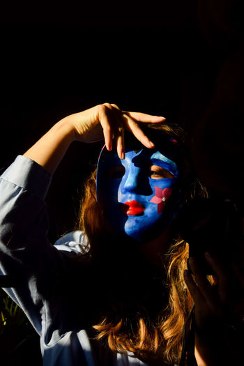 Portrait of young woman wearing mask against black background