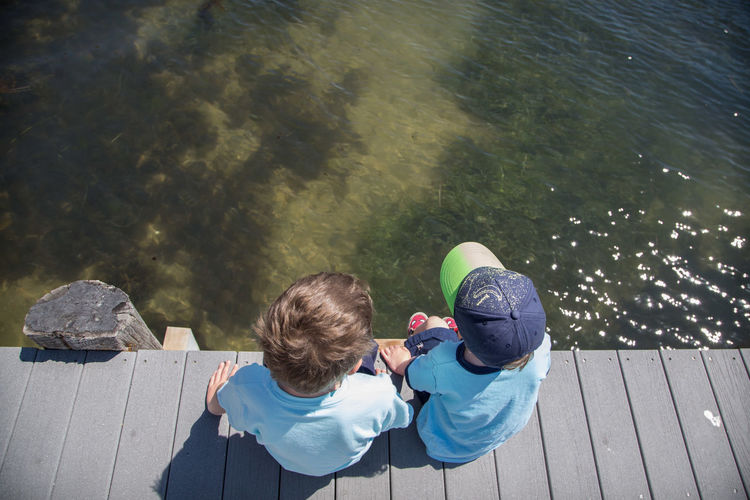 Boys Casual Clothing Childhood Day Friendship Full Length High Angle View Lake Leisure Activity Lifestyles Nature Outdoors People Pier Real People Rear View Sitting Togetherness Two People Water Wood - Material