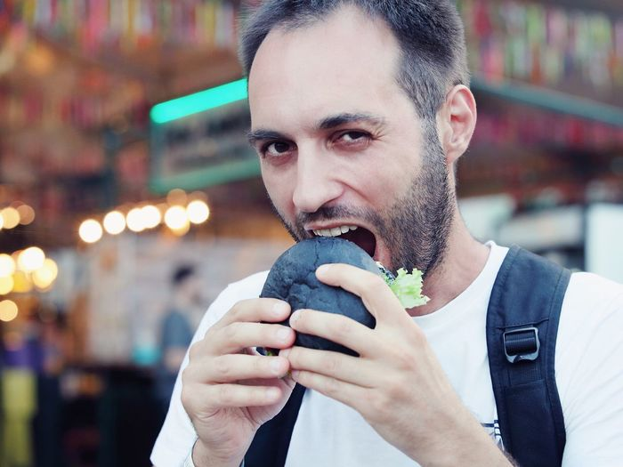 Close-Up Portrait Of Man Eating Burger