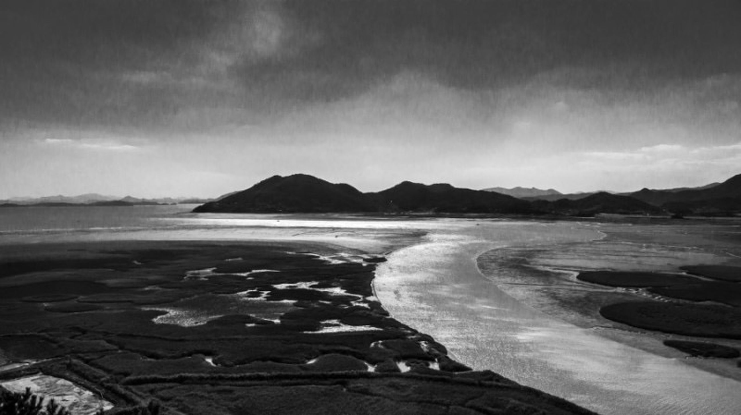 water, tranquil scene, sky, tranquility, scenics, sea, beach, beauty in nature, mountain, nature, shore, coastline, cloud - sky, idyllic, sand, rock - object, non-urban scene, cloud, remote, day