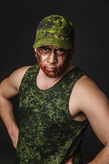 Portrait of soldier against black background