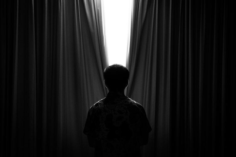 Rear view of man standing against curtain in darkroom