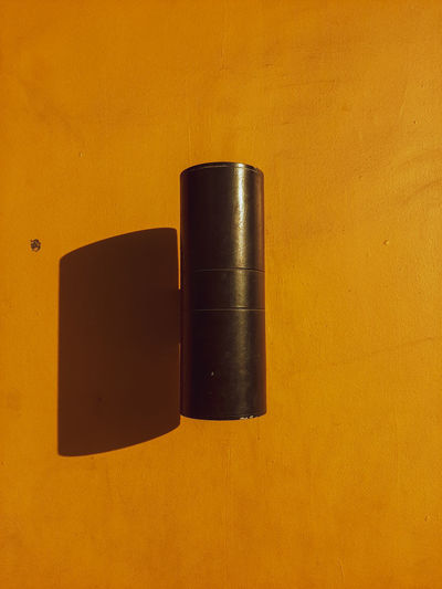 Close-up of metal object against orange background