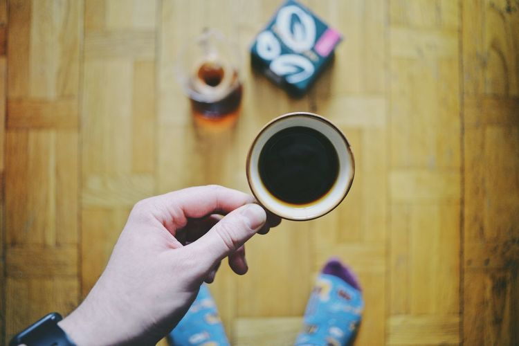 Hand holding coffee cup on floor
