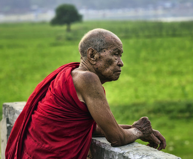 Senior monk in traditional clothing standing outdoors