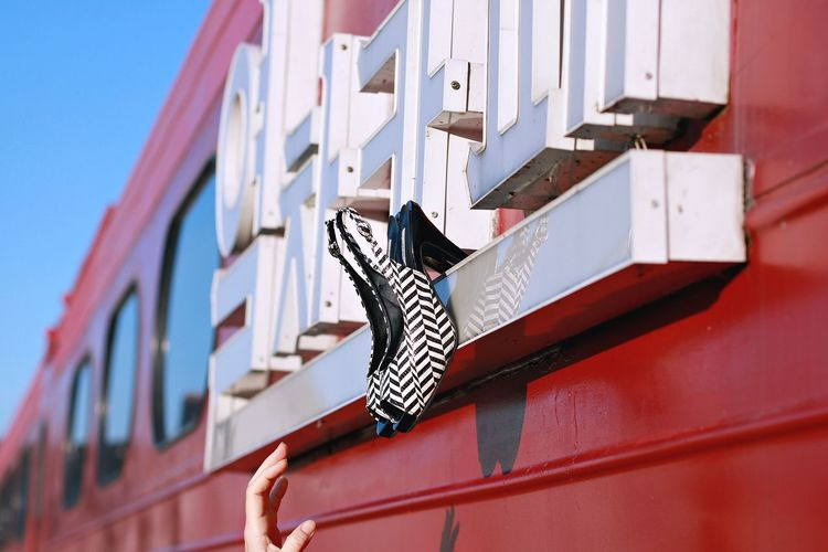 Cropped hand of woman reaching towards high heels stuck on train