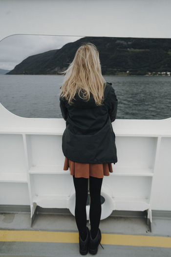 Rear view of woman standing on railing against sea