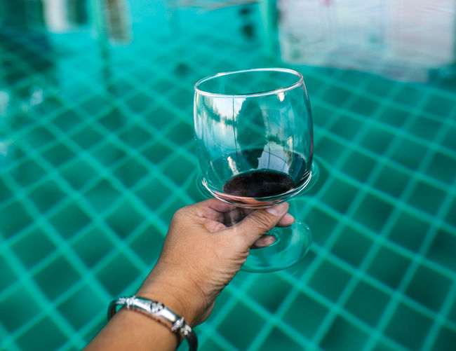 Cropped image of man drinking glass in swimming pool