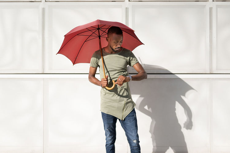 Man holding umbrella standing against wall