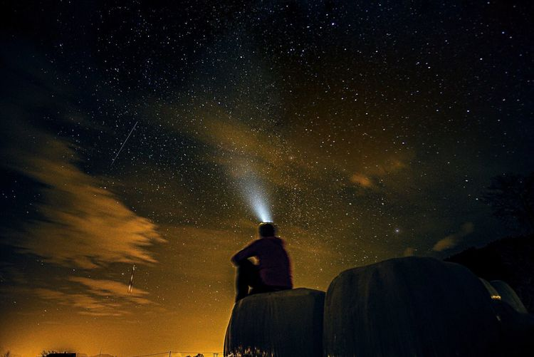Low angle view of man against sky at night