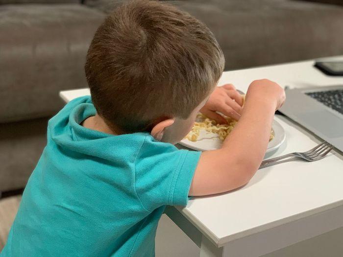 Boy eating noodles at home
