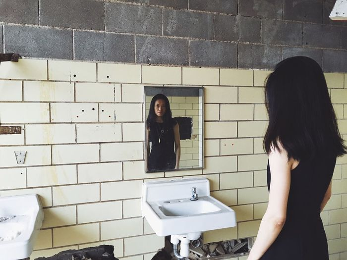 Woman standing by mirror at abandoned building