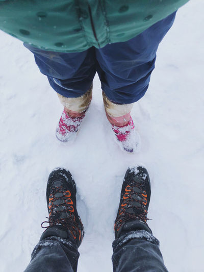 High angle view of father and child winter shoes on snow