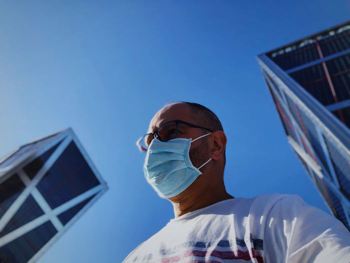 Low angle portrait of man against clear blue sky