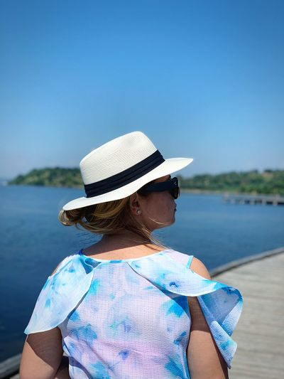 Rear view of woman wearing hat looking away while standing against sea