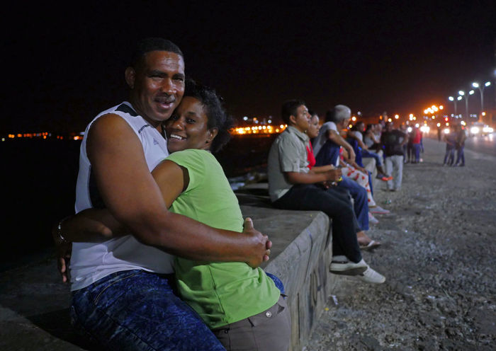 A couple enjoys their embrace while hanging out on a warm spring evening on the Malecon in Havana, Cuba. Casual Clothing Cities At Night Enjoyment Fun Happy Hug Illuminated Leisure Activity Lifestyles Love Malecón, La Habana Night Night Photography Outdoors Portrait Smiles Street Photography Streetphotography The Street Photographer - 2016 EyeEm Awards Feel The Journey