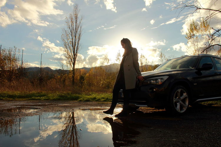 Woman standing by car against sky