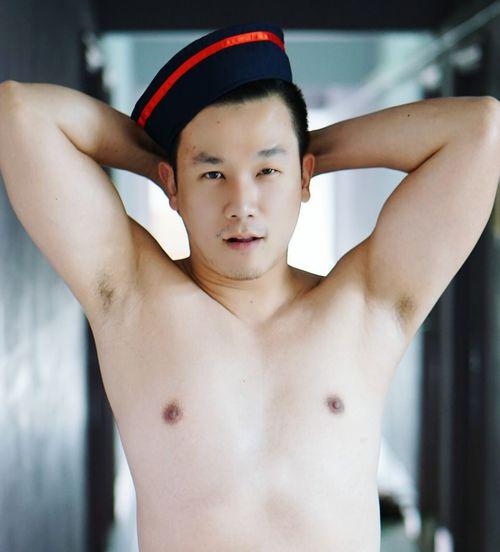 Portrait of shirtless man wearing cap in corridor