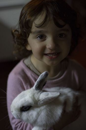 Portrait of cute girl with a white rabbit