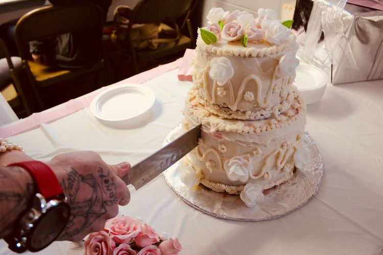 Cropped hands of couple cutting wedding cake