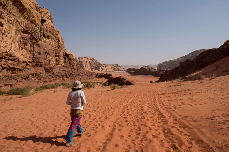 Woman trekking in the desert. Wadi Rum, Jordan Cliffs Desert Deserts Around The World Hiking Jordan Rocky Solo Traveler! Traveling Trekking Wadi Rum Walking Around Woman Arid Arid Landscape Caucasian Desert Landscape Female Landscape Mountain Nature Sand Sand Dune Sandstone Solo Traveller Trekker