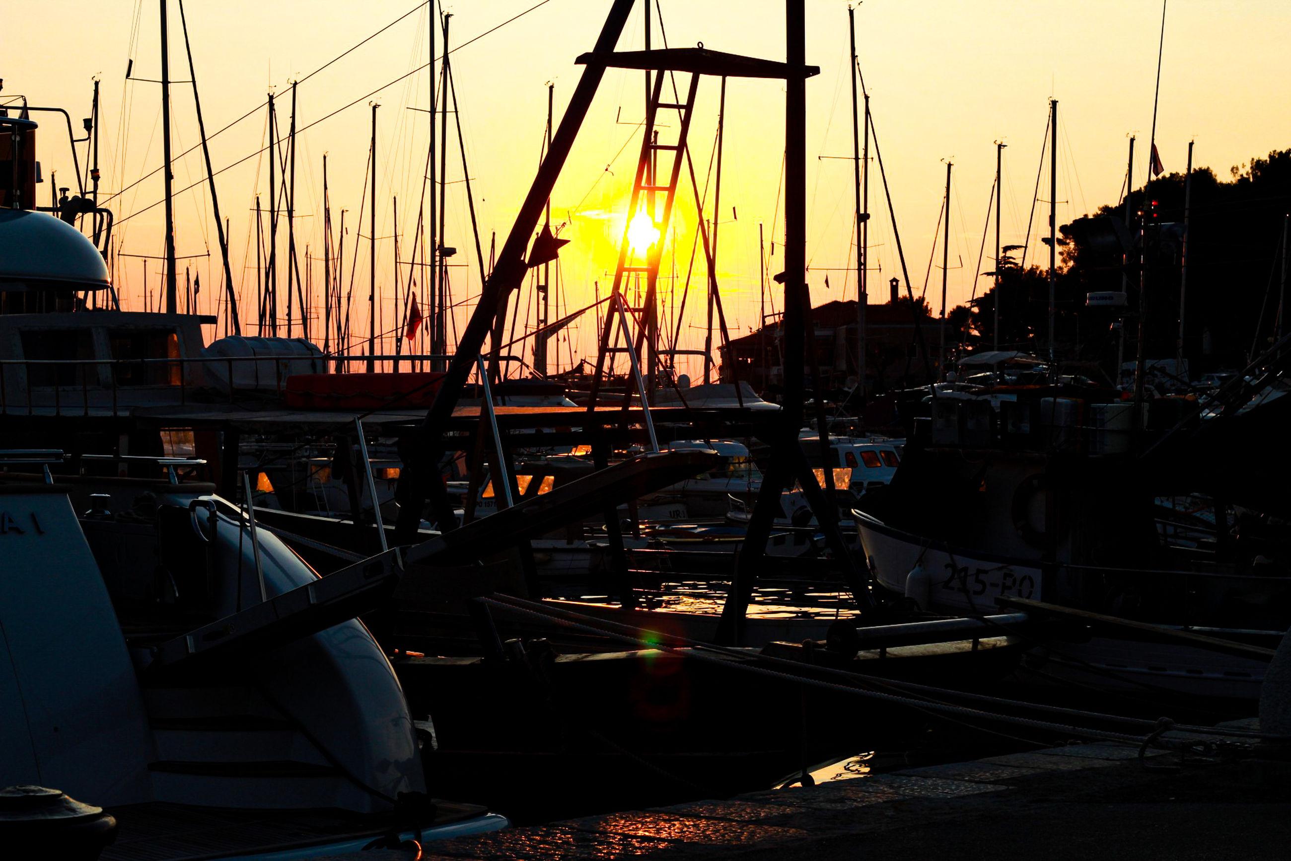 nautical vessel, sunset, transportation, water, sky, mode of transportation, sailboat, harbor, mast, moored, nature, architecture, pole, sun, no people, orange color, silhouette, sunlight, built structure, outdoors, yacht, marina, port