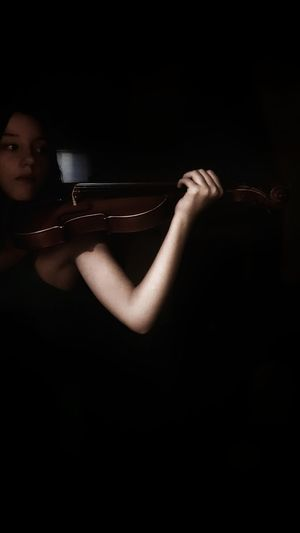 Portrait of beautiful young woman playing in the dark