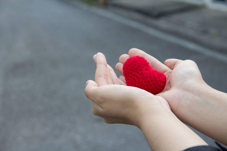 Close-Up Of Hands Holding Red Heart