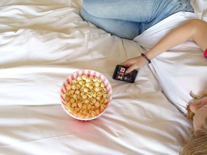 High angle view of woman holding popcorn on bed