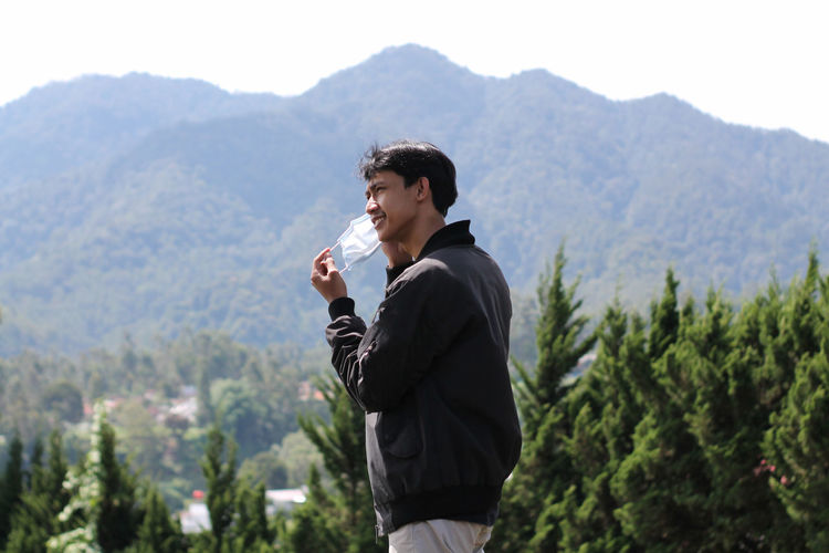 Young man standing against mountains and plants