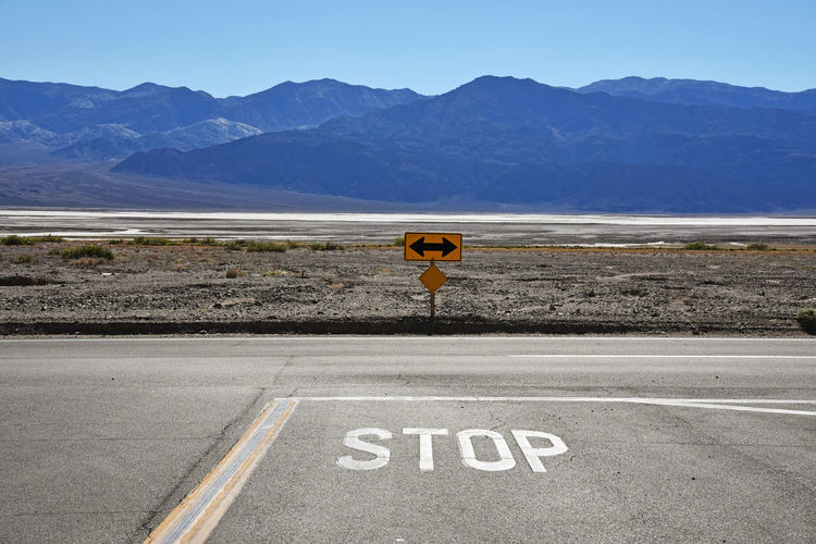 Stop text on road by mountains against clear sky