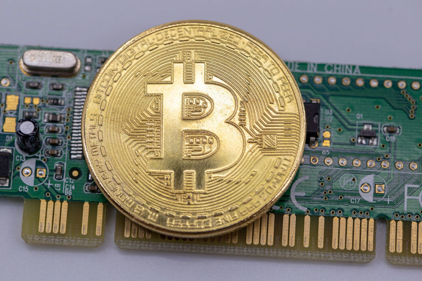 Bitcoin token on top of a circuit board. Cryptocurrency mining concept with copy space. BTC Banknotes Copy Space E-commerce Gold Isolated Virtual Bit  Bitcoin Bussiness Coin Concept Crypto Cryptocurrency Cypto Currency Euro Exchange Future Internet Minning Minning Bitcoin Money Pay Symbol White Background