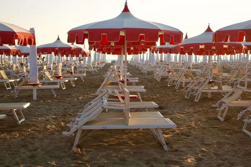 Beach Umbrella Beach Life Sunrise Day Built Structure Arts Culture And Entertainment Nature Childhood Playground In A Row Text Red Park - Man Made Space Outdoor Play Equipment Park Outdoors Chair Seat Sky Land