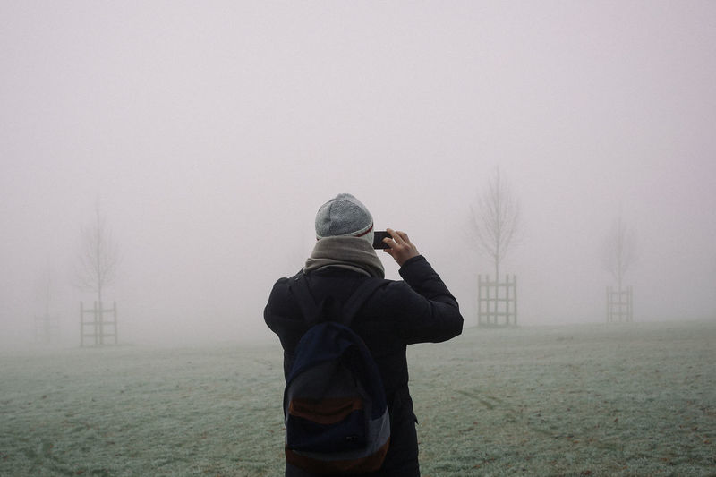 Rear View Of Man Using Mobile Phone In Foggy Weather