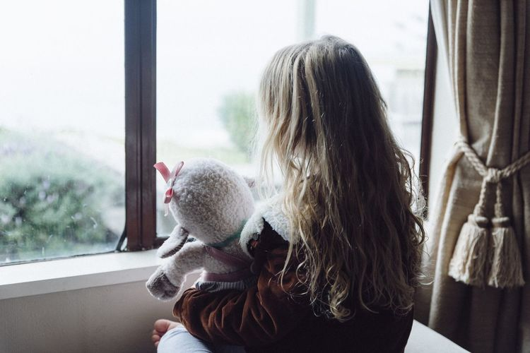 Rear view of girl holding stuffed toy while looking through window