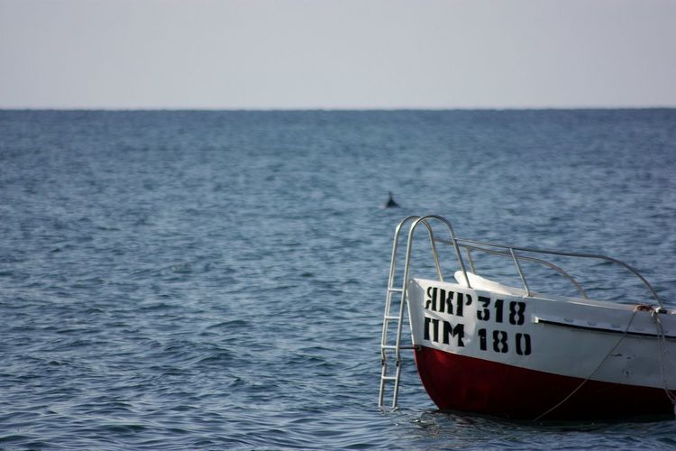 Cropped image of motorboat on sea against clear sky
