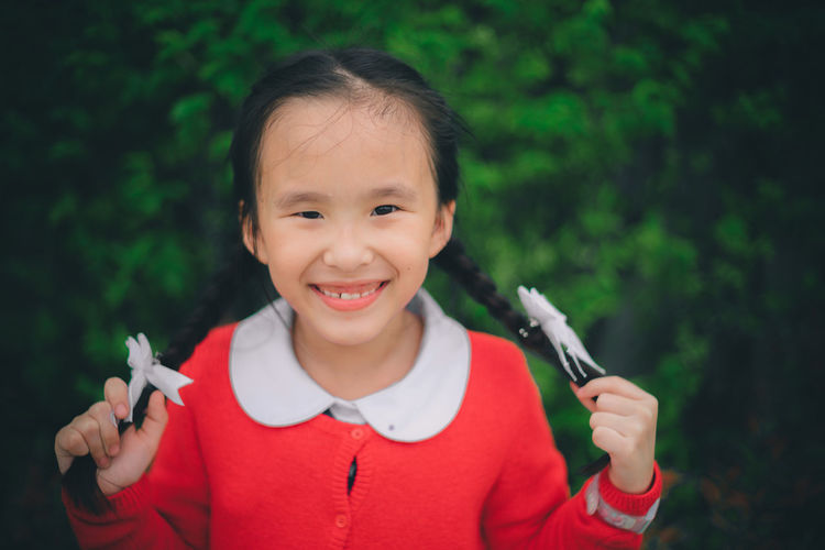 Close-up portrait of cheerful girl with pigtails against plants