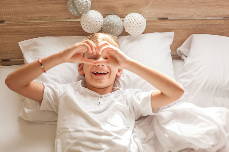 Furniture One Person Real People Childhood Indoors  Bed Lying Down Front View Happiness Child Lifestyles Lying On Back Emotion Boys High Angle View Smiling Portrait Directly Above Mouth Open Innocence Heart Shape Beauty In Nature Children Horizontal Bed