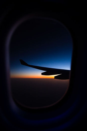 Silhouette airplane wing seen through window against sky during sunset