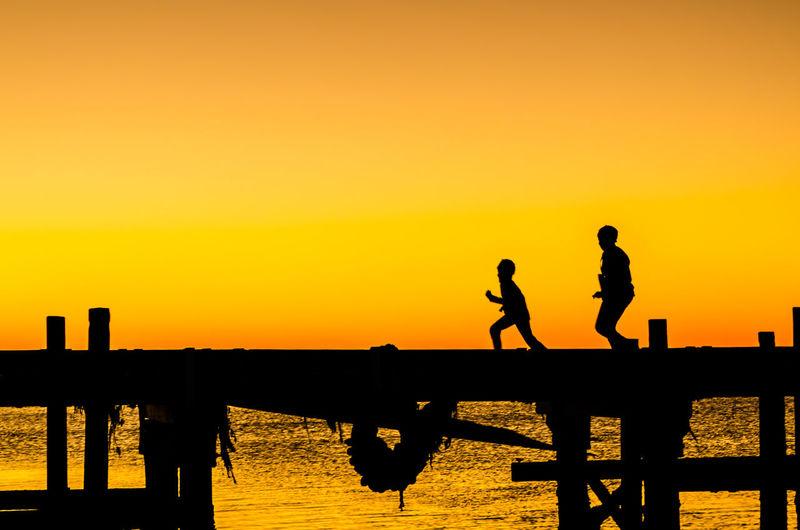Silhouette Men On Pier Against Sky During Sunset