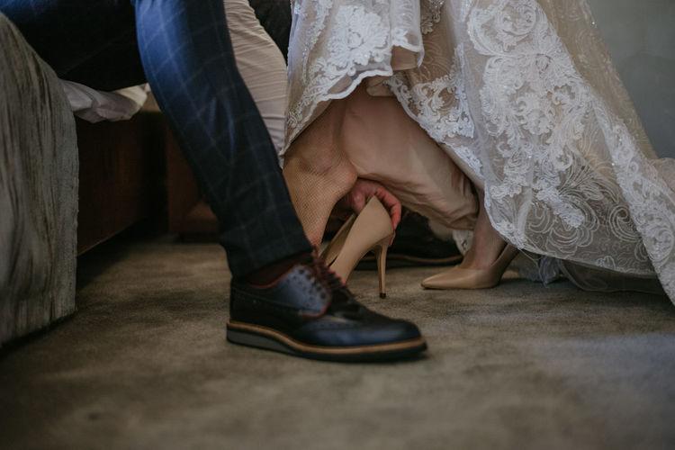 Man helping woman to put on high heels