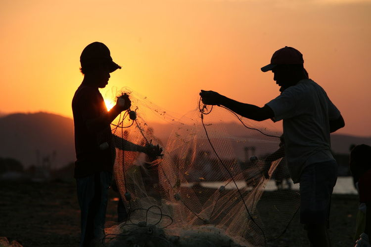 Silhouette fishermen working with net at beach during sunset