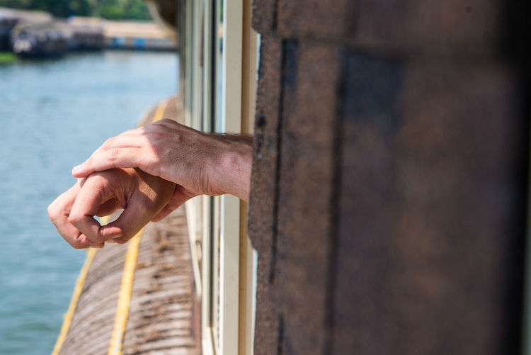 Cropped hands of men out of window against canal