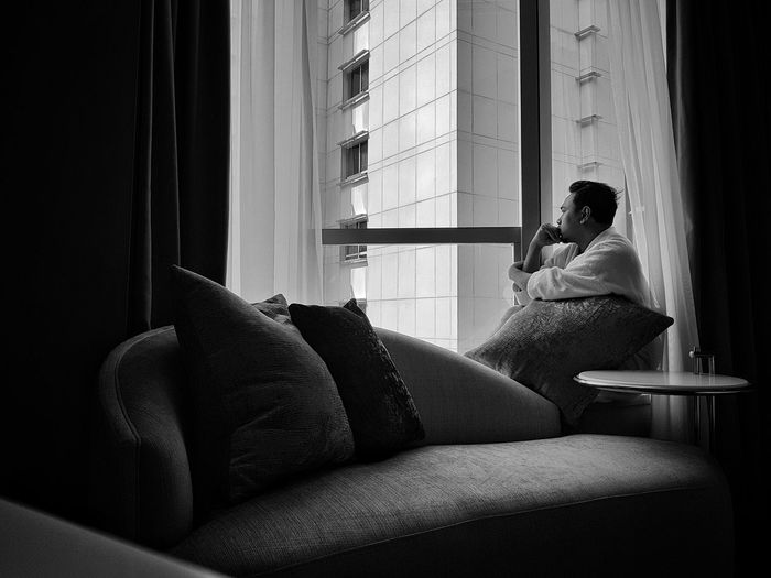 Thoughtful mid adult man looking through window while sitting at home