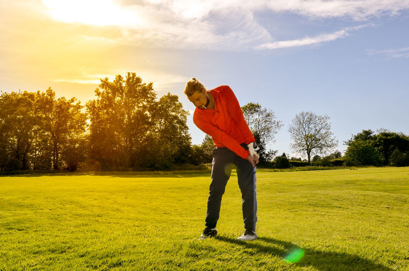 Man Playing Golf On Course Against Sky During Sunny Day