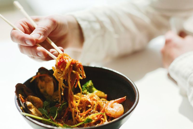 close-up of a young man eating an asian food dish Food Food And Drink Indoors  One Person Freshness Human Hand Hand Pasta Human Body Part Holding Italian Food Plate Real People Wellbeing Healthy Eating Close-up Ready-to-eat Table Asian Food Meal