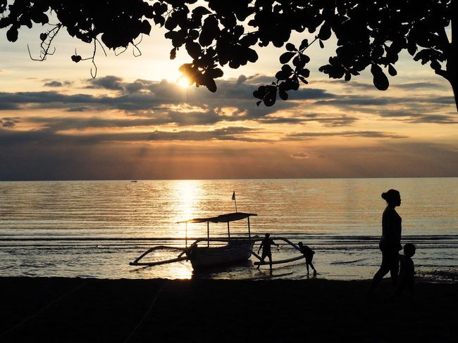 Traditional fishing boat on the seashore at sunset Lovina Bali Indonesia Sunset Silhouette Sea Scenics Water Beauty In Nature Nature Tranquility Sky Idyllic Tranquil Scene Horizon Over Water Full Length Beach Outdoors Fishing Standing Real People Lifestyles Tree Bali Beach Lovina Beach INDONESIA