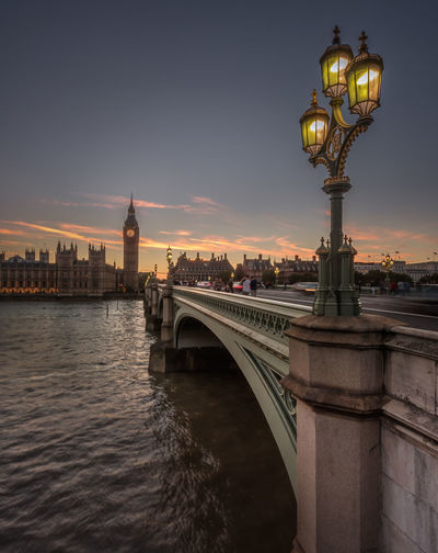 Westminster Bridge Over Thames River By Big Ben And Houses Of Parliament Against Sky During Sunset