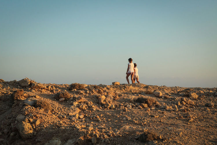 Two girls in summer walking on top of a hill by the sea Sky Real People Clear Sky Lifestyles Two People Leisure Activity Togetherness People Nature Full Length Love Copy Space Men Land Rock Solid Bonding Rock - Object Positive Emotion Couple - Relationship Girls Horizon Over Water Arid Climate Summer